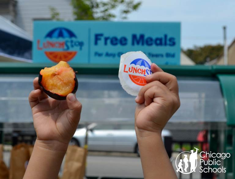 "Two child-sized hands. One hand is holding a half eaten plum and the other is holding a sticker that says ""LunchStop."""