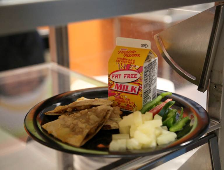 Milk, vegetables and a quesadilla on a plate within a cafeteria service line