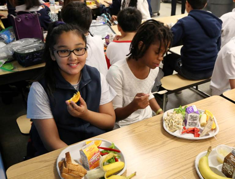 Students eating their lunches within a cafeteria