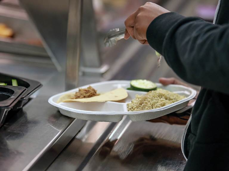 Student placing food onto their plate